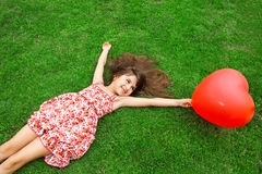 Beautiful girl lying on the grass and holding a red ball in the Stock Photo