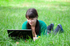 Beautiful girl lying in the grass with laptop Stock Photo