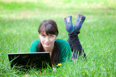 Beautiful girl lying in the grass with laptop Royalty Free Stock Photography