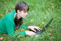 Beautiful girl lying in the grass with laptop Stock Photography