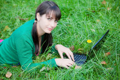 Beautiful girl lying in the grass with laptop Royalty Free Stock Image