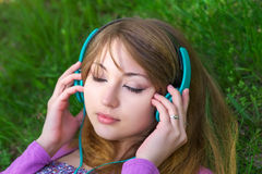 Beautiful girl lying on the grass and listening music Royalty Free Stock Photos
