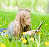 Beautiful girl lying on the grass and using tablet computer Royalty Free Stock Photos