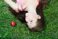 Beautiful girl lying on the gree grass near red apple Stock Images