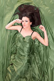 Beautiful girl lying on green. Beautiful girl with long dark hair lying on green fabric stock photos