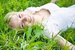 Beautiful girl is lying on green grass Stock Image