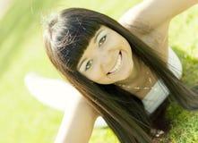 Beautiful girl lying on green grass Stock Photo
