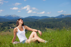 Beautiful girl lying on green grass field. Landscape royalty free stock image