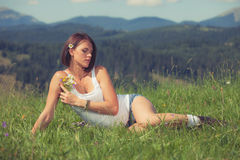 Beautiful girl lying on green grass meadow. And holding flowers in her hand Royalty Free Stock Photos