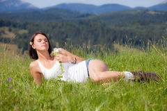 Beautiful girl lying on green grass meadow. And holding flowers in her hand royalty free stock photo