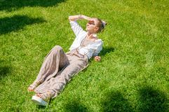 Beautiful girl lying on green grass and smile enjoy sunny day in park. Summer concept. Boho style. Beautiful girl lying on green grass and smile enjoy sunny day stock photo
