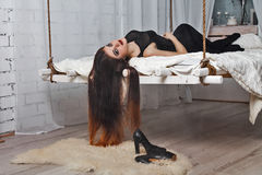Beautiful girl lying on hanging bed suspended from the ceiling Royalty Free Stock Photography