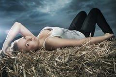 Beautiful girl lying on haystack Stock Image