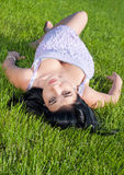 Beautiful girl lying on her back in lawn. Stock Images