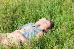 Beautiful girl lying on the meadow. Beautiful girl lying on the summer meadow royalty free stock photography