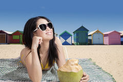 Beautiful girl lying near the beach huts Stock Photo