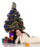 Beautiful girl lying near a dressed Christmas tree Stock Photography