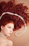 Beautiful girl is lying with a pearl necklace Stock Images