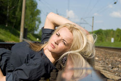 Beautiful girl lying on the rails Royalty Free Stock Image