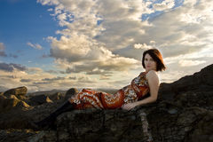 Beautiful girl lying on rocks Stock Images