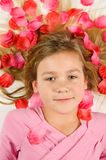 Beautiful girl lying in rose petals. On white stock photography