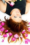 Beautiful girl lying in rose petals Royalty Free Stock Photography