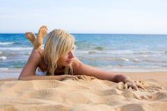 Beautiful girl lying on the sand Stock Image