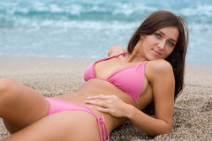 Beautiful girl lying on a sandy beach Stock Photos