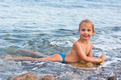 Beautiful girl lying at the seashore Stock Photography