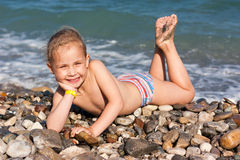 Beautiful girl lying at the seashore Stock Photos