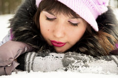 Beautiful girl lying in the snow Royalty Free Stock Photography