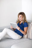 Beautiful girl lying on the sofa with a computer tablet Stock Image