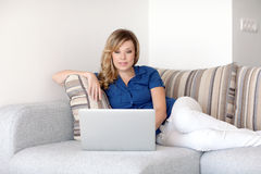 Beautiful girl lying on the sofa with a laptop computer Stock Photography