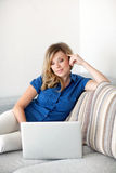Beautiful girl lying on the sofa with a laptop computer Royalty Free Stock Photography