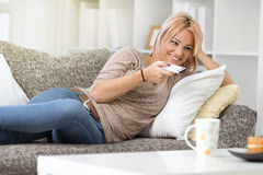 Beautiful girl lying in sofa with remote controller Royalty Free Stock Image