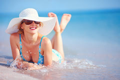 Beautiful girl lying in surf on the beach Stock Image