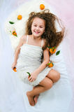 Beautiful girl lying among tangerines Stock Photo