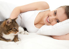 Beautiful girl lying in white bedding with cat Royalty Free Stock Photos
