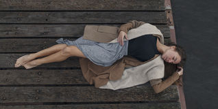 Beautiful girl lying on the wooden berth. Beautiful sad girl lying on the wooden berth with her eyes close in warm clothes. Melancholy royalty free stock images