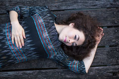 Beautiful  girl lying on a wooden podium. Stock Photography
