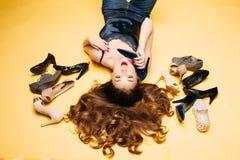 Girl lying on yellow among many fashionable shoes.