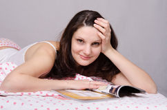 Beautiful girl with a magazine in bed Royalty Free Stock Photos