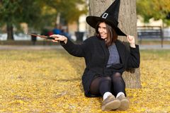 A girl sit at the floor in a magic wizard hat in the park. A beautiful girl in a magic hat waving a magic wand in an autumn park sitting on a leaf near a tree Royalty Free Stock Photos