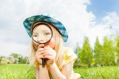 Beautiful girl with magnifier laying on the grass Royalty Free Stock Photo