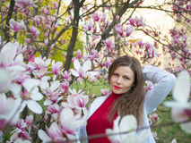 Beautiful girl among magnolia pink blossom sping tree flowers.  Stock Photo