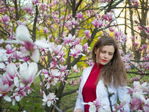Beautiful girl among magnolia pink blossom sping tree flowers.  Royalty Free Stock Images