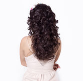 Beautiful girl make her hair curls on long black hair decorated with a wreath of flowers Royalty Free Stock Photo