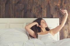 Beautiful girl make selfie lie in bed Royalty Free Stock Photos