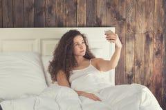 Beautiful girl make selfie lie in bed Stock Photo