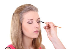 Beautiful girl with make-up brush over white Royalty Free Stock Images